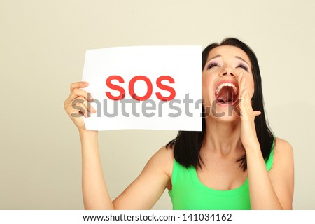 Girl showing stop sign on grey background - stock photo