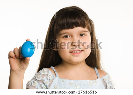 Girl shows an Easter egg of dark blue colour on a white background