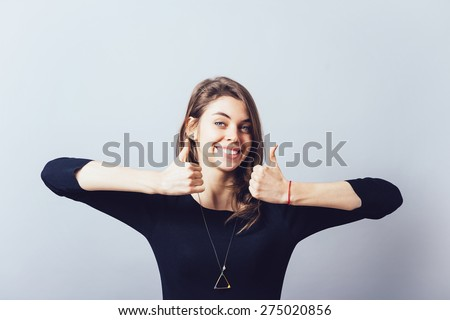 Girl shows big thumb up - stock photo