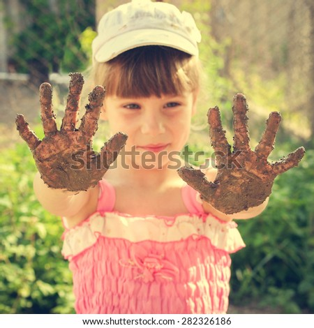 Girl shows her dirty hands. Toned image  - stock photo