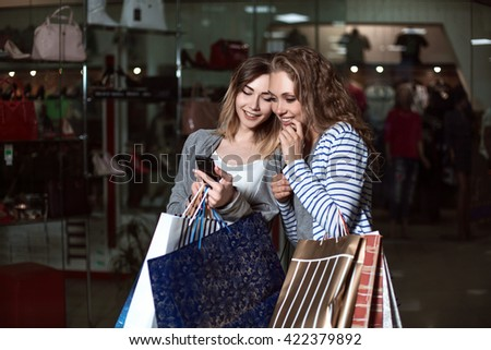 girl shows on a mobile phone is something his girlfriend. Fashion Shopping two ladies Portrait. Beauty Woman with Shopping Bags in Shopping Mall. Shopper. Sales. Shopping Center - stock photo