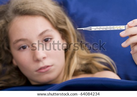 girl sick in bed, having over 39?C /102?F fever. with a shallow depth of field - focus on thermometer. - stock photo
