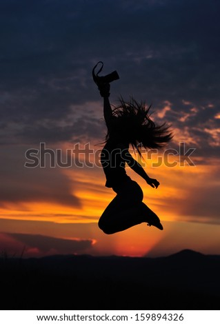 Girl silhouette jumping with photo camera in hand in sunset. Low key shot.