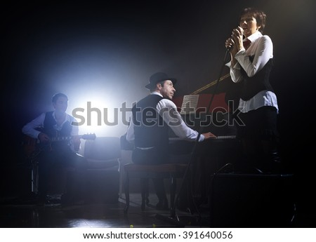 Girl singing into retro microphone to the accompaniment of piano and guitar