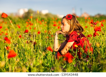 Girl sit in the poppies field and enjoy the nature