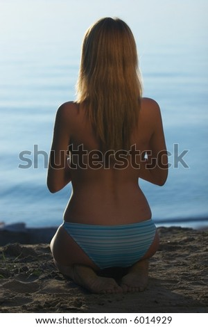 girl sit on sand, back to camera - stock photo