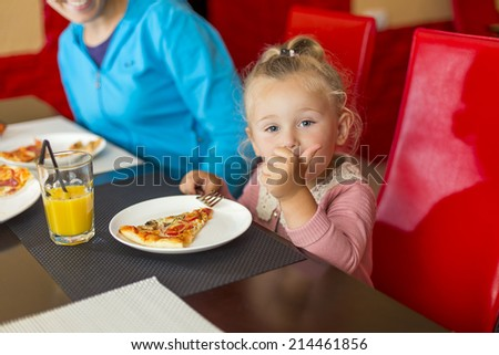 girl sits at a table and eating pizza - stock photo