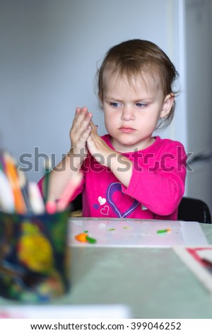 Girl sits at the table and hands the ball rolls out of plasticine