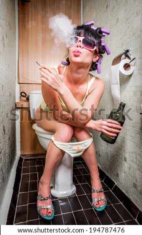 Girl sits in a toilet with an alcohol bottle - stock photo