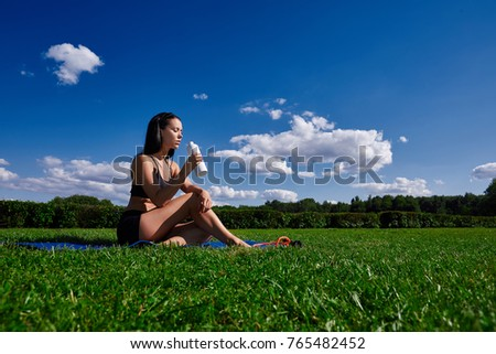 Girl sits in Park on a grass and holding a bottle of water.