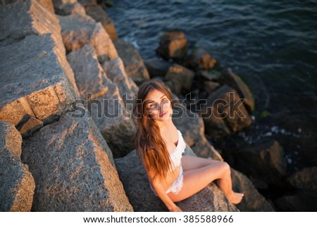 girl sits on a stone and looks at the top