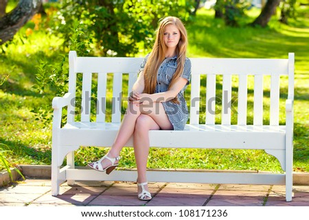 girl sits on a white bench in park having thrown a foot on a foot - stock photo