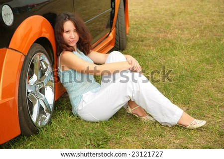 Girl sits on grass near car - stock photo