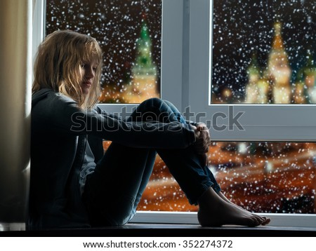 Girl sits on the window. Outside, winter city. Snow falls. Girl in jeans barefoot. Outside, Moscow. Evening night. The girl is sad - stock photo