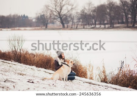 girl sits with his dog in the park and looks into the distance - stock photo