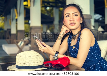 girl sitting alone holding smartphone in coffee shop