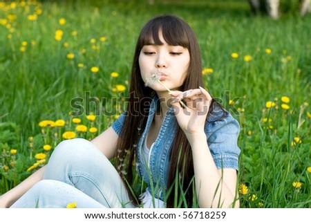 Girl sitting among dandelions - stock photo