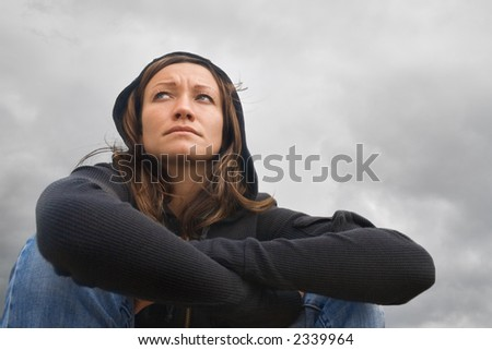 Girl sitting and contemplating on a background of a cloudy sky - stock photo