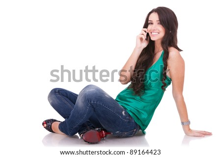 girl sitting and  talking on a cell phone on white background - stock photo