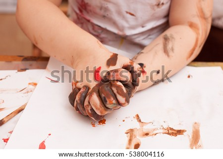 girl sitting at the table and draws paints