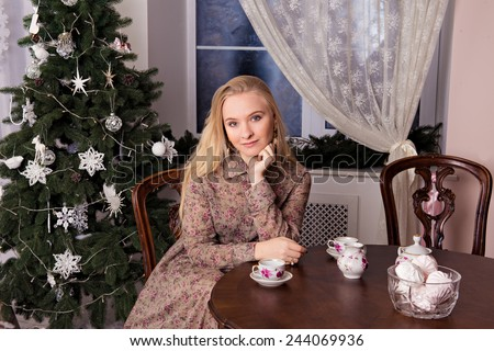 girl sitting at the table. on the table is a cup of tea. on the background Christmas tree and a large window. girl waits for a Man.
