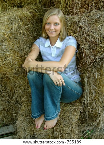 Girl sitting barefoot, posed in Hay Bales. - stock photo
