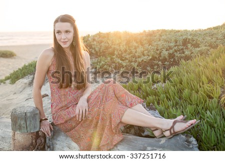 Girl sitting by the beach at sunset - stock photo