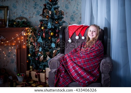 girl sitting in a chair wrapped in a blanket in the background of fireplace and Christmas tree - stock photo