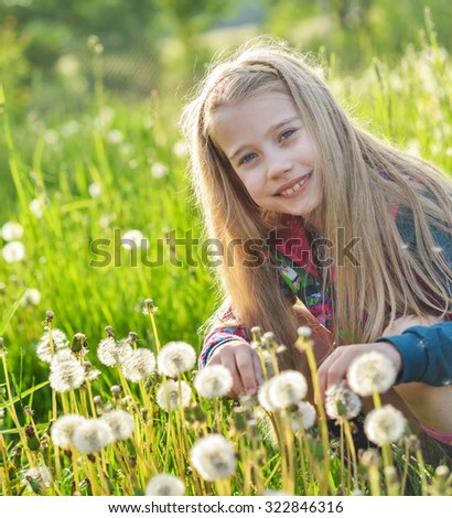 Girl sitting in a field of dandelions
