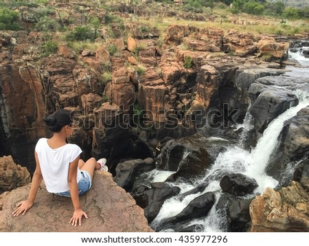 Girl sitting in a rock overlooking a waterfall in a rocky landscape at Blyde River Canyon in South Africa.