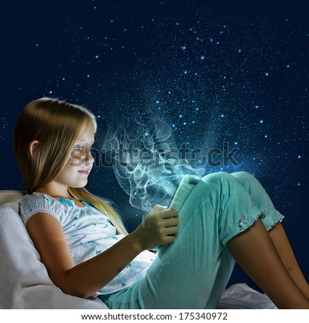 Girl sitting in bed and playing with tablet pc