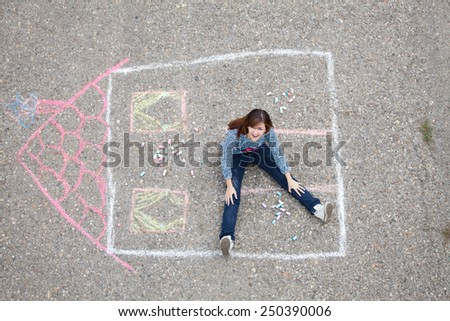 Girl sitting in drawn house - stock photo