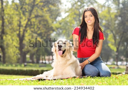 Girl sitting in park with her pet dog - stock photo