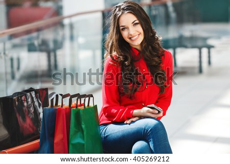 Girl sitting in shopping mall, looking at camera and smiling. Beautiful girl holding phone in one hand and colorful shopping bags lying near her. Leg put on other leg. Wearing red blouse and jeans. - stock photo