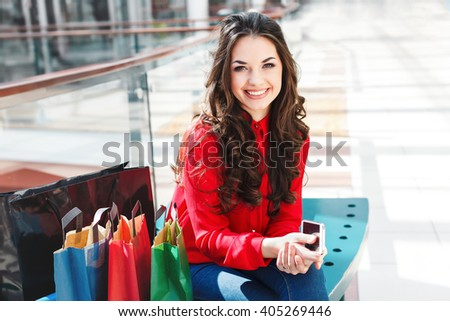 Girl sitting in shopping mall, looking at camera and smiling. Beautiful girl holding phone in one hand and colorful shopping bags lying near her. Wearing red blouse and jeans. Indoor - stock photo