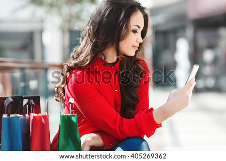 Girl sitting in shopping mall, looking at phone and smiling. Beautiful girl holding phone in one hand and colorful shopping bags lying near her. Wearing red blouse and jeans. Indoor, waist up, profile - stock photo