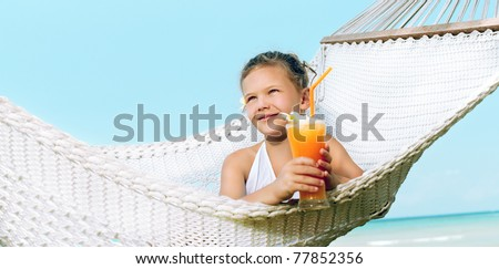 girl sitting in the hammock with cocktail on the beach smiling - stock photo