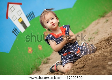 Girl sitting in the sand  playing  - stock photo