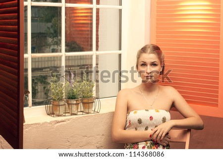 Girl sitting near an open window of the house - stock photo
