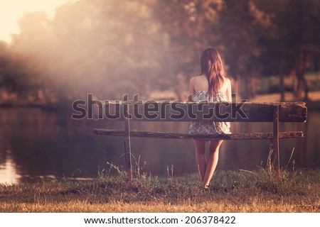 Girl sitting on a bench - stock photo