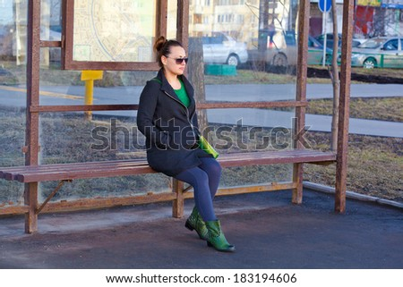 Girl sitting on a bench waiting for transport at the bus stop - stock photo