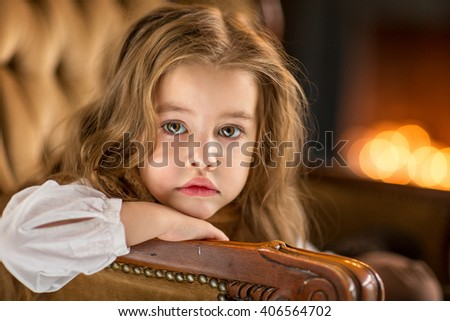 Girl sitting on a chair by the fireplace and looks at us, a large portrait, sad