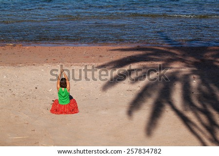 girl sitting on a dirty beach with shade from the palm tree, Egypt, Dahab  - stock photo