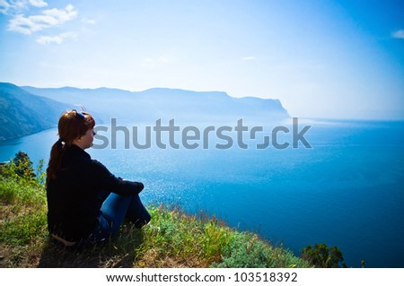 girl sitting on a mountain and looking at a seascape