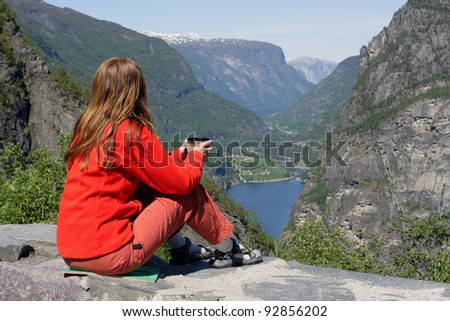 girl sitting on a parapet and looking at the fine landscape - stock photo
