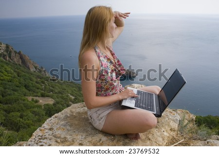 Girl sitting on a rock beside the sea with a laptop - stock photo