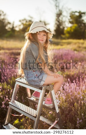 Girl sitting on a stepladder in fairy field of lavender. Summer  - stock photo