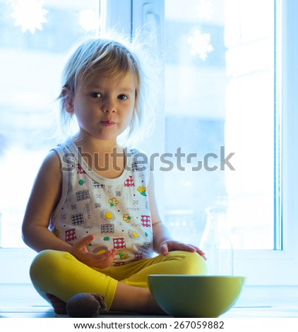 Girl sitting on a windowsill and eating - stock photo
