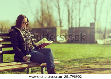 Girl sitting on a wooden bench, reading a book and drinking coffee, outdoors