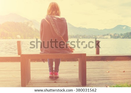 Girl sitting on a wooden pier near water. - stock photo